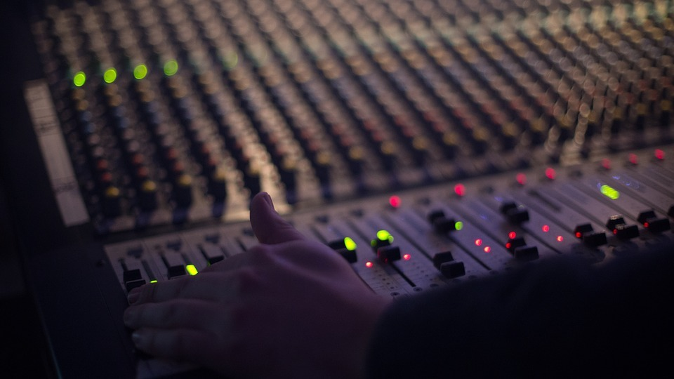 audio engineer with hand on mixer