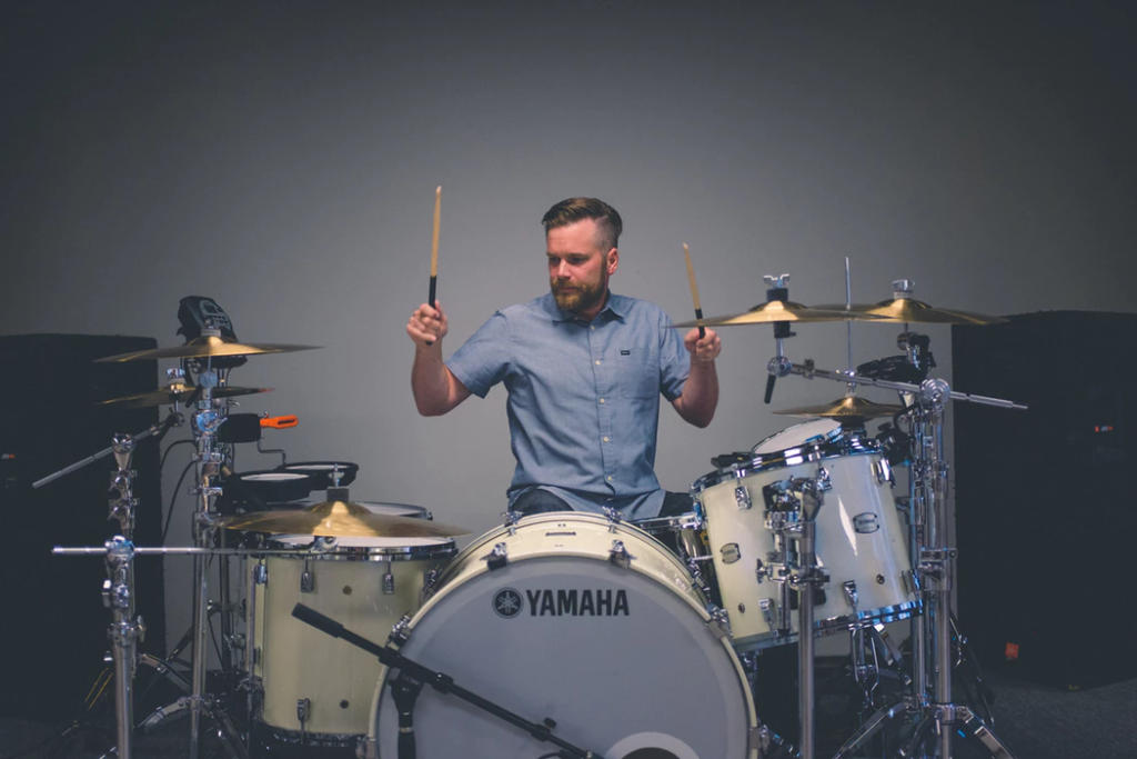 Man playing drums and hitting cymbals with drum sticks