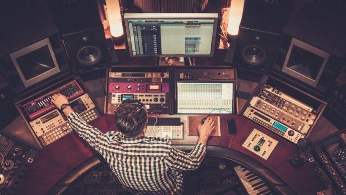 engineering working in recording studio with computer, speakers.