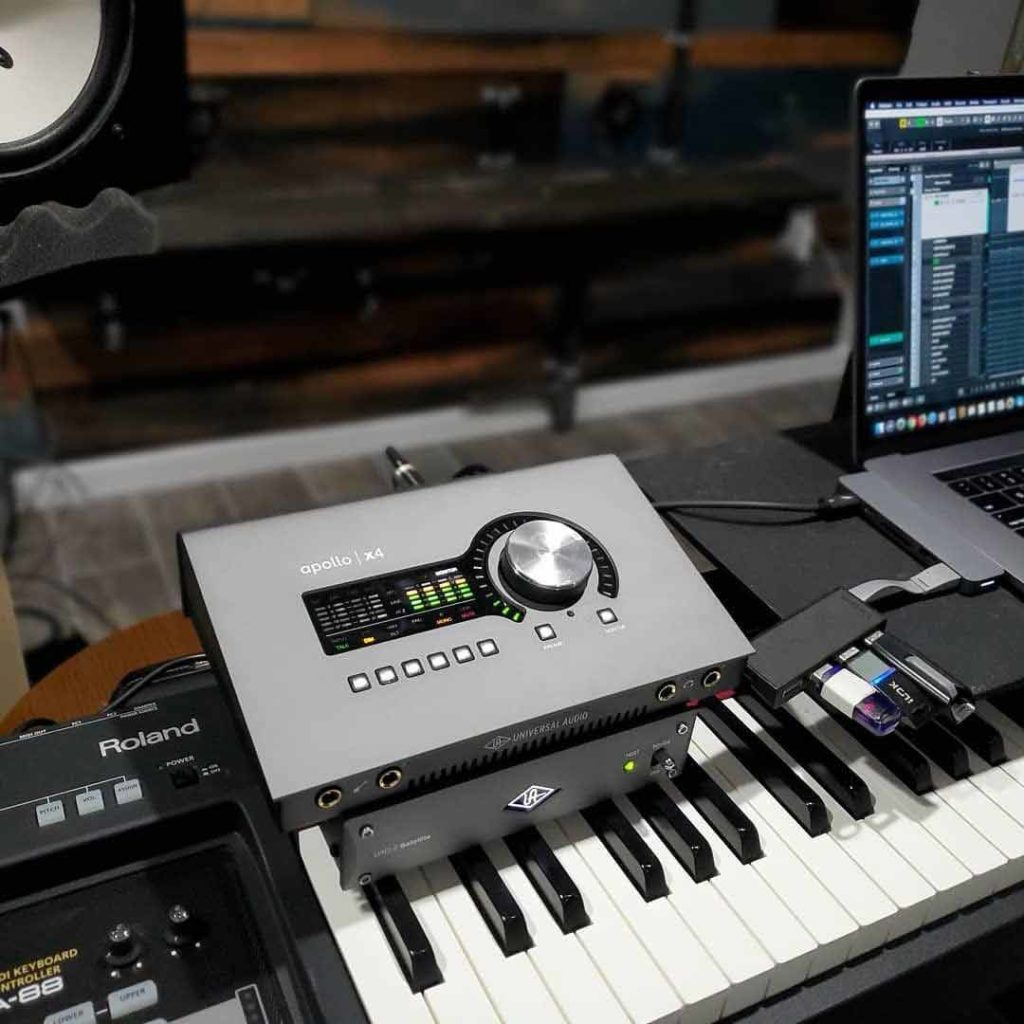 audio interface on keyboard with laptop and studio monitors